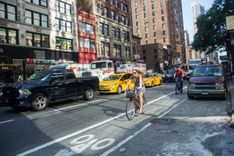 Cyclist bypasses a traffic jam through a cycle lane on West 32nd Street, New York. The volume of cyclists is ballooning whilst injuries have dropped slightly. Copyright Yingqian Chen 2014.